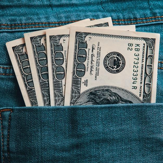 Cento banconote americane in contanti nella tasca posteriore dei suoi jeans Foto Premium