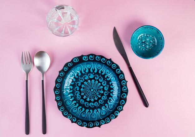 Ceramica turca decorata piatto blu con nuovi posate nero di lusso su rosa, vista dall'alto Foto Premium