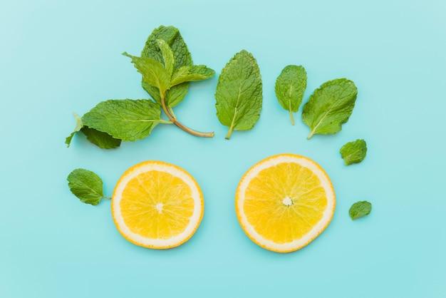 Cerchi di agrumi e foglie di menta su sfondo Foto Gratuite
