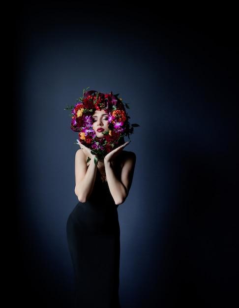 Cerchio colorato fatto di fiori freschi sul viso della bella ragazza, donna vestita in abito stretto nero su sfondo blu scuro Foto Gratuite