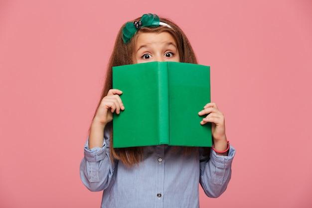 Cerchio da portare da portare della ragazza sveglia divertendosi mentre leggendo il libro interessante con gli occhi spalancati Foto Gratuite