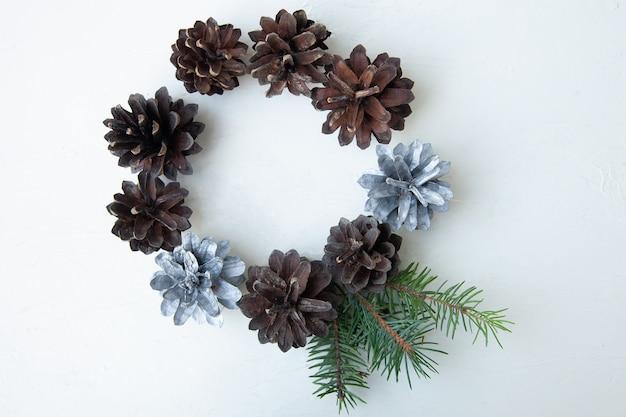 Cerchio di pigne su una superficie bianca. composizione natalizia naturale. biglietto di auguri. disteso. vista dall'alto Foto Premium