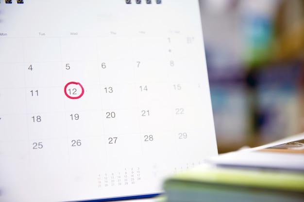 Cerchio rosso sul calendario per la pianificazione aziendale e la riunione. Foto Premium