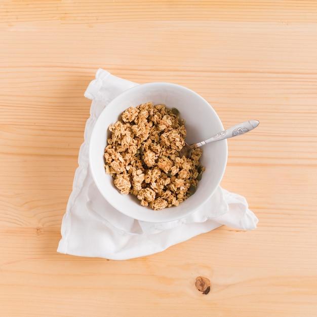Cereale e cucchiaio della prima colazione del granoturco dell'avena nella ciotola bianca sopra il tovagliolo bianco sullo scrittorio di legno Foto Gratuite