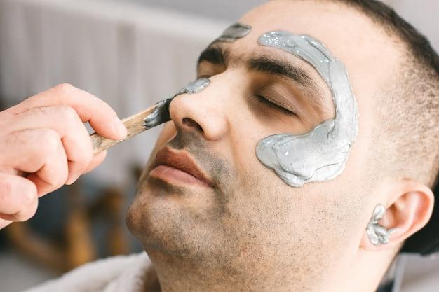Ceretta viso maschile. il barbiere rimuove i capelli shugaring dal viso dell'uomo turco. Foto Premium