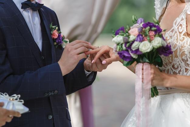 Cerimonia di nozze all'aperto vicino. lo sposo indossa l'anello nuziale della sposa. giorno del matrimonio. sposi emotivi si stanno scambiando fedi nuziali. felice coppia appena sposata. Foto Premium