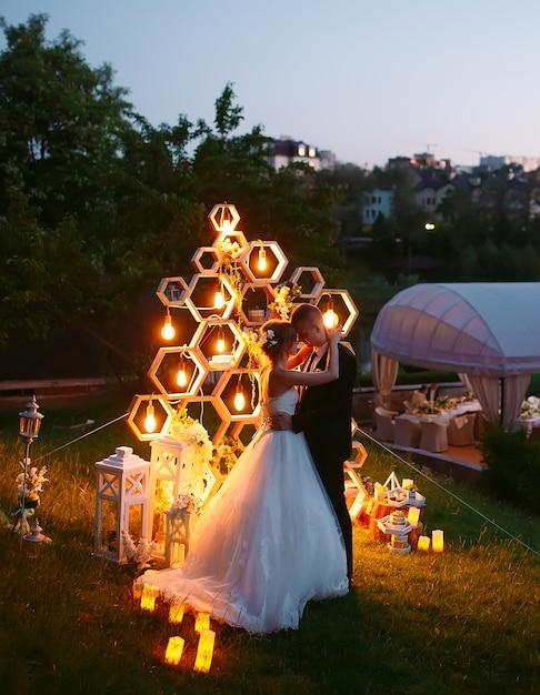 Cerimonia nuziale serale. la sposa e lo sposo sono sullo sfondo dell'arco nuziale. Foto Premium