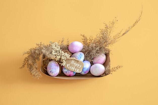 Cestino con le uova di pasqua su una parete isolata colorata Foto Gratuite
