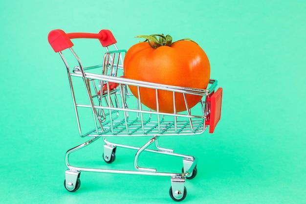 Cestino del supermercato, inside è un pomodoro maturo. Foto Premium