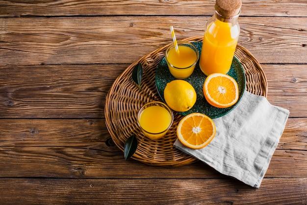 Cesto alto angolo con bottiglia e bicchiere di succo d'arancia Foto Gratuite