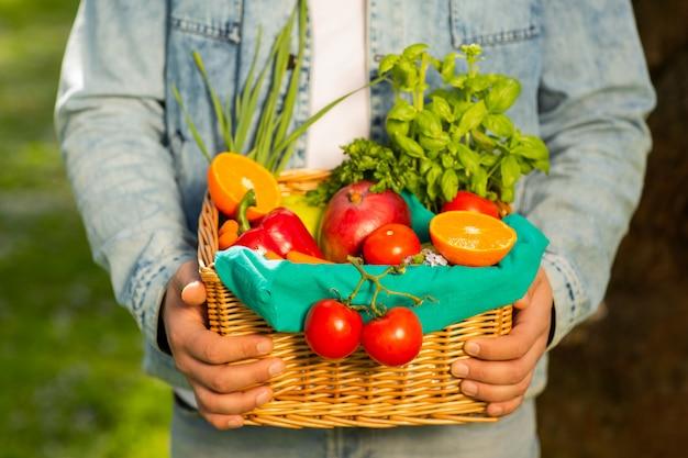 Cesto con frutta e verdura nelle mani di uno sfondo di agricoltore della natura. di stile di vita sano Foto Premium