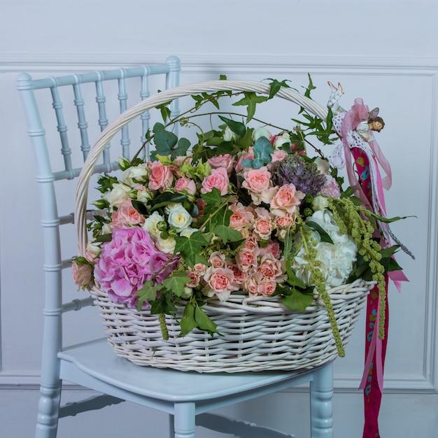 Cesto di fiori misti in piedi su una sedia bianca Foto Gratuite