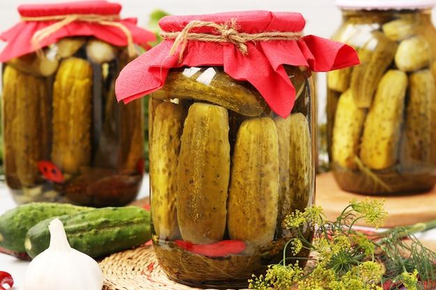 Cetrioli marinati in barattoli, aglio e aneto su bianco Foto Premium
