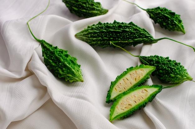 Cetriolo amaro o momordica sul fondo bianco del tessuto. cucina esotica. disteso Foto Premium