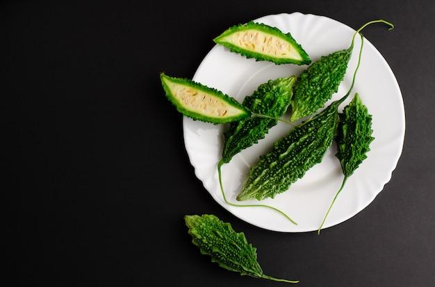 Cetriolo amaro sul piatto bianco su sfondo nero. cucinando . copia spazio, vista dall'alto. Foto Premium