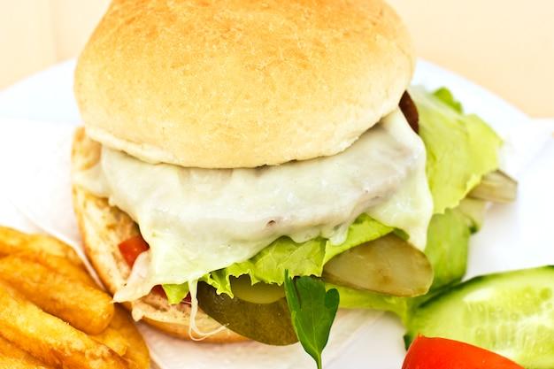 Cheeseburger con patatine fritte, cetrioli a fette e pomodori Foto Premium