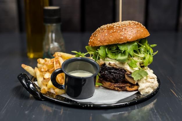 Cheeseburger con verdure, salsa all'aglio e patatine fritte su un tavolo di legno Foto Premium