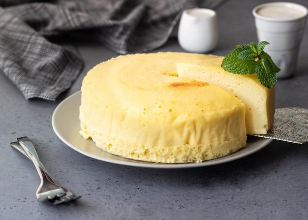 Cheesecake di cotone giapponese con menta su un piatto grigio. Foto Premium