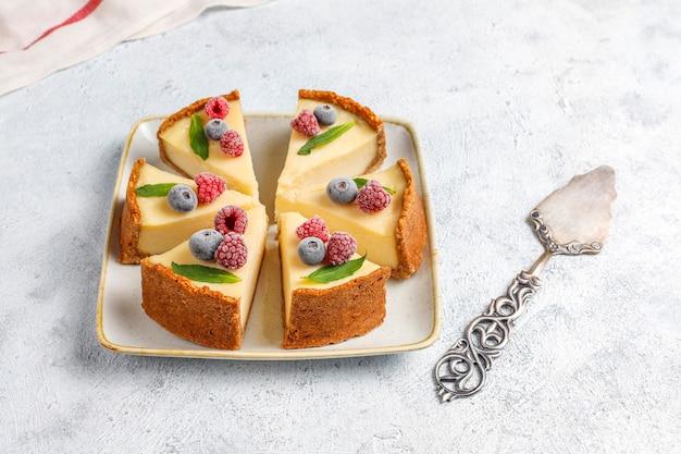 Cheesecake di new york fatto in casa con frutti di bosco congelati e menta, dessert biologico sano, vista dall'alto Foto Gratuite