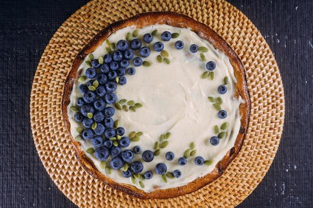 Cheesecake fatta in casa con mirtilli freschi e semi di zucca Foto Premium