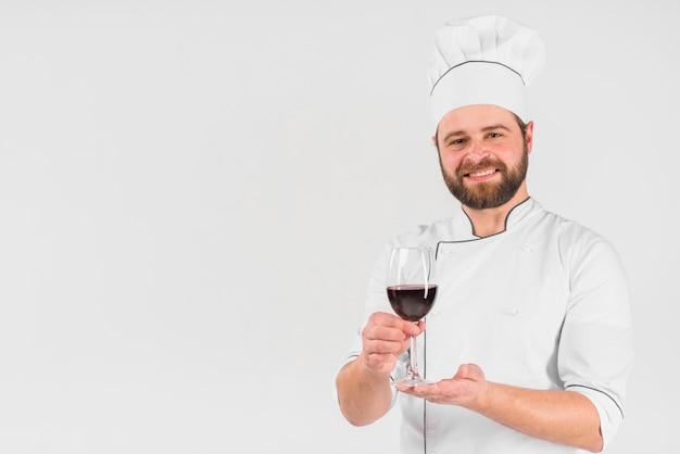 Chef che offre un bicchiere di vino Foto Gratuite