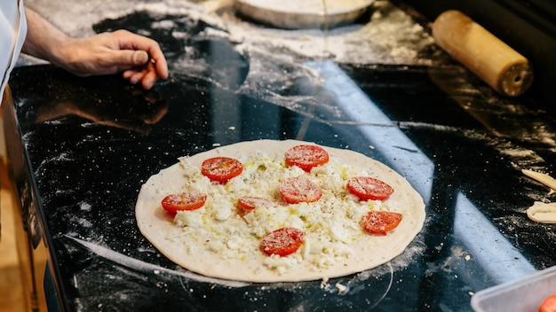 Chef che prepara la pizza caprese bianca aggiungendo l'olio d'oliva sulla pasta. Foto Premium