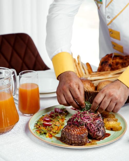 Chef che serve bistecche di manzo alla griglia con patatine fritte, ketchup e insalata Foto Gratuite
