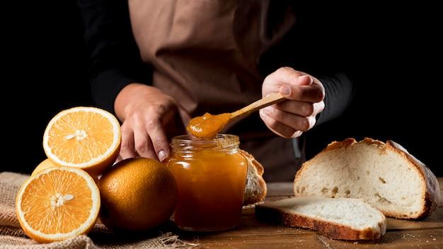 Chef con barattolo di marmellata di arance Foto Gratuite