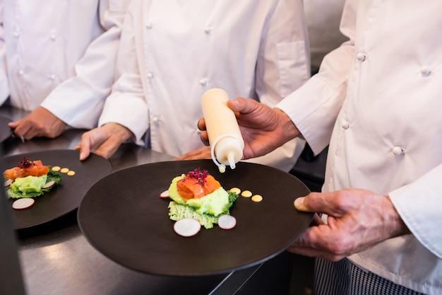 Chef decorare un piatto di cibo Foto Premium