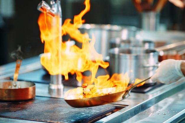 Chef di cucina verdure in padella wok. Foto Premium
