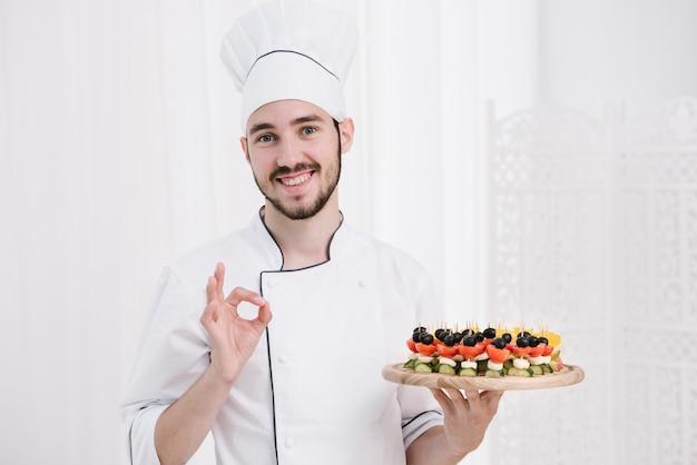 Chef di smiley con cappello tenendo la piastra Foto Gratuite