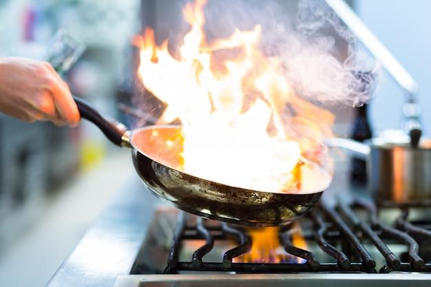 Chef in cucina del ristorante a piano cottura con padella Foto Premium