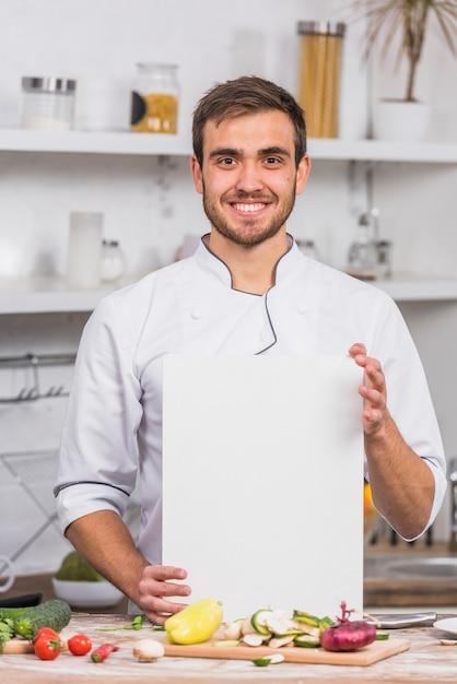 Chef in cucina mostrando il modello di carta Foto Gratuite