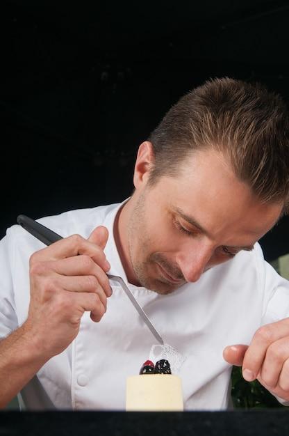Chef positivo che decora il gelato con frutti di bosco Foto Gratuite