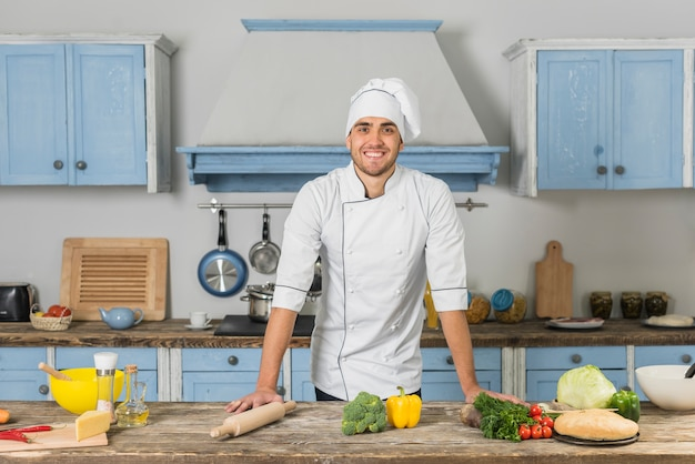 Chef sorridente in cucina Foto Gratuite