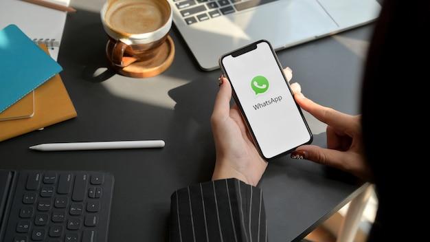Chiang mai, tailandia - 1 ° febbraio 2020: iphone femminile della tenuta con lo schermo di whatsapp. whatsapp è un'applicazione di messaggistica Foto Premium