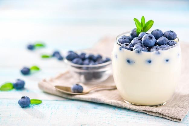 Chiaro barattolo di yogurt con i mirtilli più su fondo di legno Foto Premium