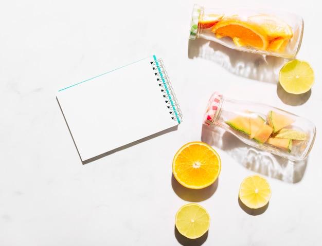 Chiaro taccuino arancione e bottiglie di vetro con agrumi tagliati Foto Gratuite