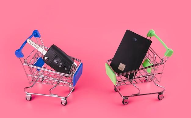 Chiave dell'automobile e carta di viaggio nella carta di acquisto blu e verde contro fondo rosa Foto Gratuite