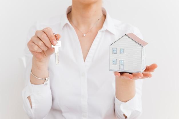 Chiave della tenuta e della donna e piccola casa di carta sopra fondo bianco Foto Gratuite