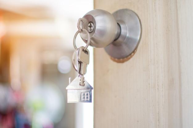 Chiave di casa sulla porta. focalizzazione morbida. Foto Premium