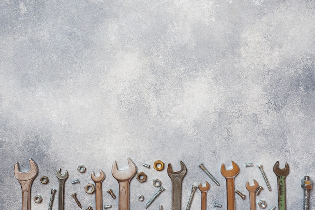 Chiavi, bulloni degli strumenti e dadi su fondo concreto grigio con lo spazio della copia. Foto Premium