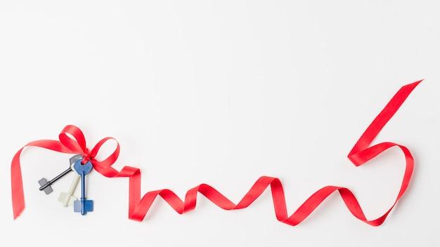 Chiavi con nastro rosso isolato su sfondo bianco Foto Gratuite