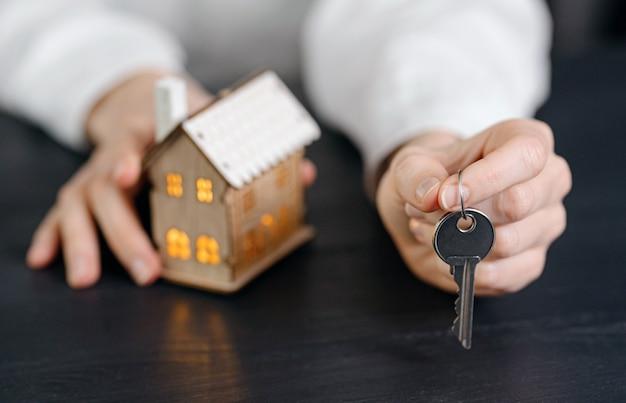 Chiavi di casa nelle mani di una donna e un piccolo modello di una casa con finestre luminose nelle vicinanze. concetto di acquisizione della tua casa Foto Premium