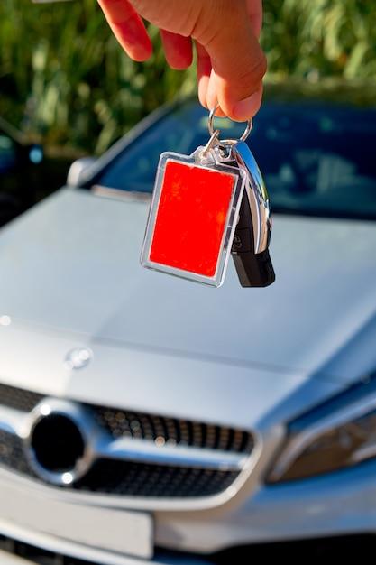 Chiavi maschii dell'automobile della tenuta con l'automobile su fondo. Foto Premium