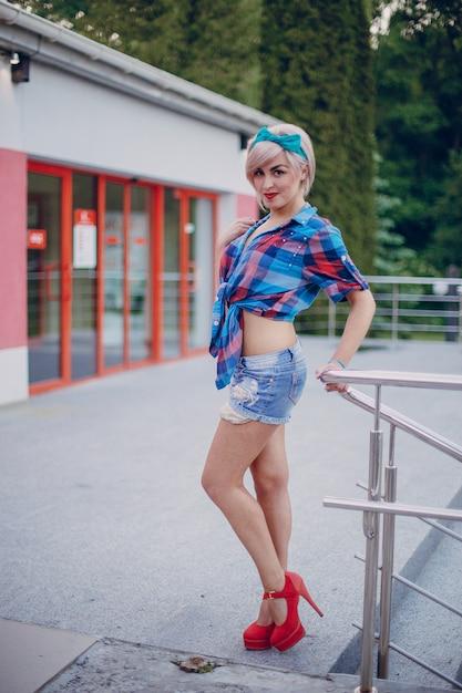 Chica joven posando en una pared roja Foto Gratuite