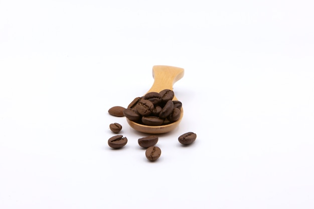 Chicchi di caffè arrostiti sul cucchiaio di legno isolato su priorità bassa bianca. Foto Premium