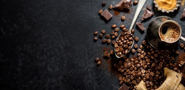 Chicchi di caffè con oggetti di scena per fare il caffè Foto Premium