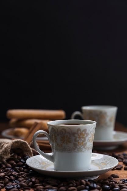 Chicchi di caffè del primo piano vicino alla tazza Foto Gratuite