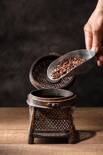 Chicchi di caffè di versamento della mano in contenitore d'annata Foto Gratuite